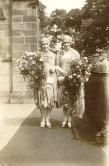 1920s Bridesmaids wearing cloche hats with huge bouquets of flowers