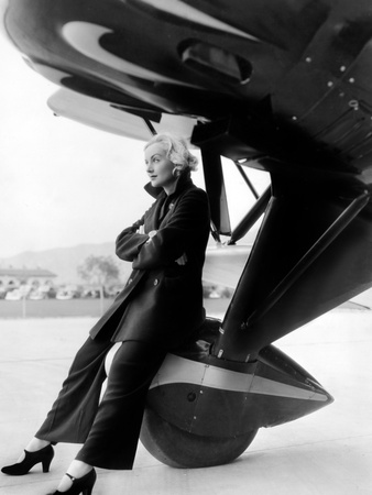 Carole Lombard sitting on an aircraft wheel