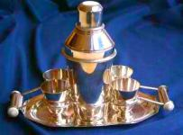 Cocktail shaker set on tray with metal cups